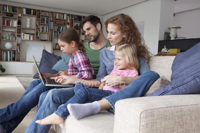 Пара, сидящая с двумя маленькими дочерьми на диване в гостиной и смотрящая на ноутбук — стоковое фото