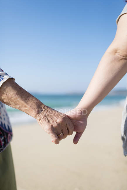 Elderly woman and young woman holding hands on the beach — Stock Photo