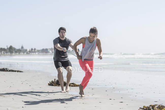Молодий чоловік і жінка, які здійснюють на пляжі — стокове фото