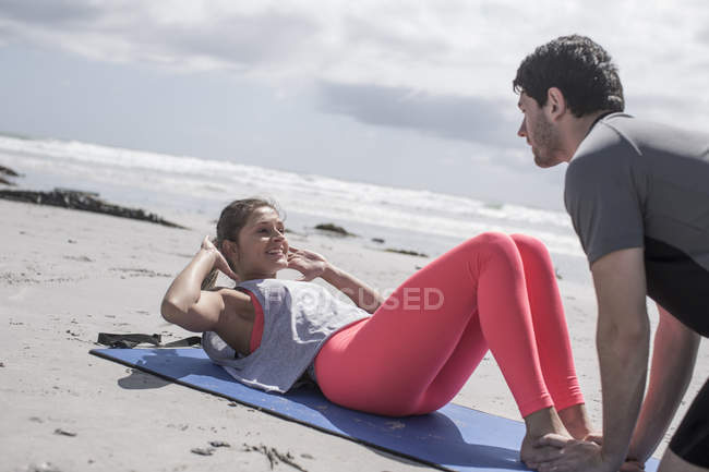 Young man and woman exercising on beach — Stock Photo