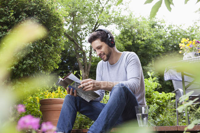Relaxed man sitting in garden with headphones and magazine — Stock Photo