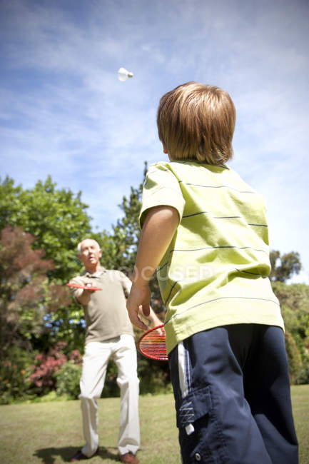 Little boy playing badminton with his grandfather — Stock Photo