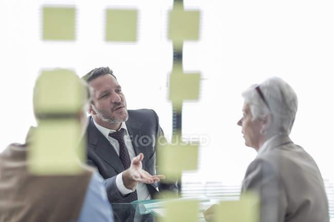 Trois hommes d'affaires confiants discutent au bureau — Photo de stock