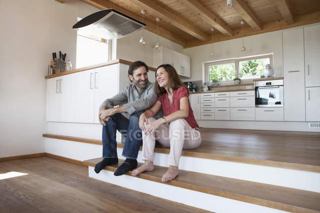 Зрелая пара сидит на полу и говорит о будущем — стоковое фото