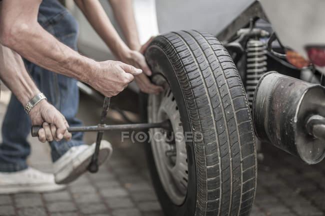 Закри людські руки, зміни шин автомобіля — стокове фото