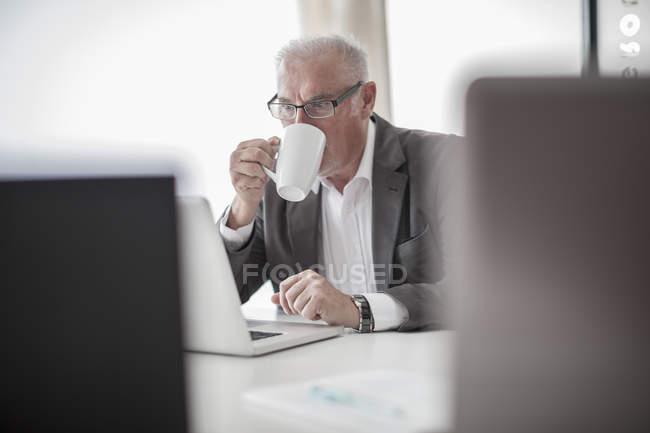 Homme d'affaires au bureau en utilisant un ordinateur portable dans un bureau moderne — Photo de stock
