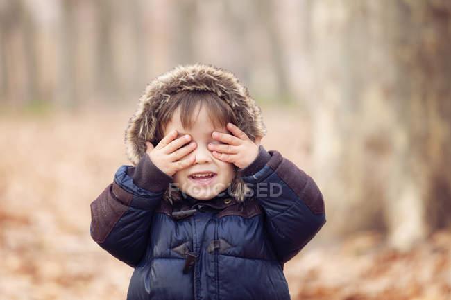 Garotinho no casaco com capuz, fechando os olhos com as mãos — Fotografia de Stock