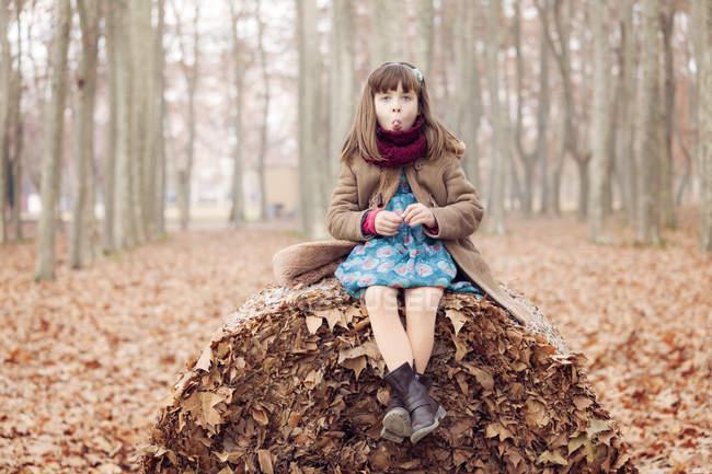 Jovem sentada na bola de folhas de autum — Fotografia de Stock