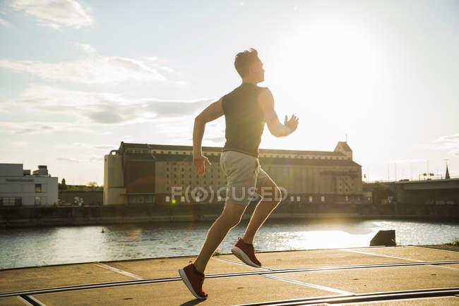 Jeune homme courant au bord de la rivière — Photo de stock
