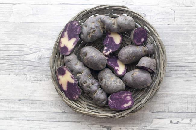 Pommes de terre en tranches et ensemble violets dans un panier en osier rond — Photo de stock