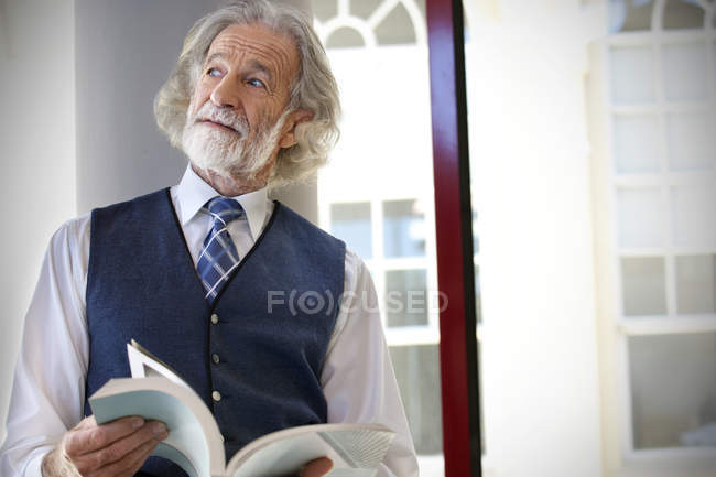 Senior professor holding book next to window — Stock Photo
