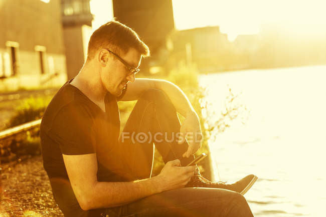 Man with smartphone relaxing at city harbour in evening twilight — Stock Photo