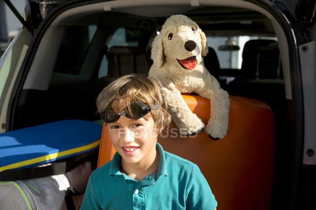 Smiling boy in car boot with swimming goggles and cuddly toy — Stock Photo