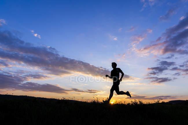Silueta del hombre corriendo al atardecer - foto de stock