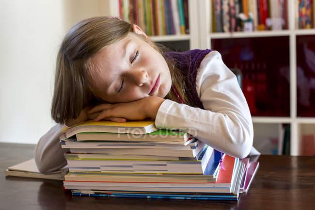 Jeune fille dormant sur la pile de livres scolaires — Photo de stock