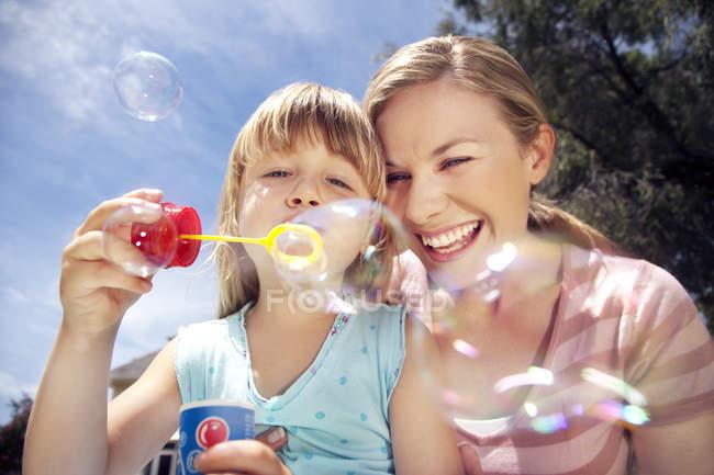 Жінка і малою донькою дме мильних бульбашок — стокове фото