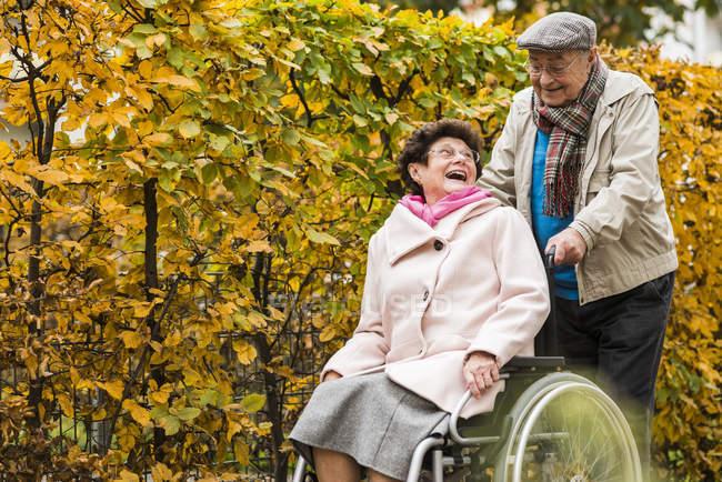Senior schubst Frau im Rollstuhl — Stockfoto