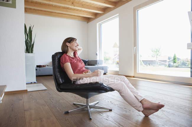 Donna matura seduta rilassata nel suo soggiorno, bevendo caffè — Foto stock