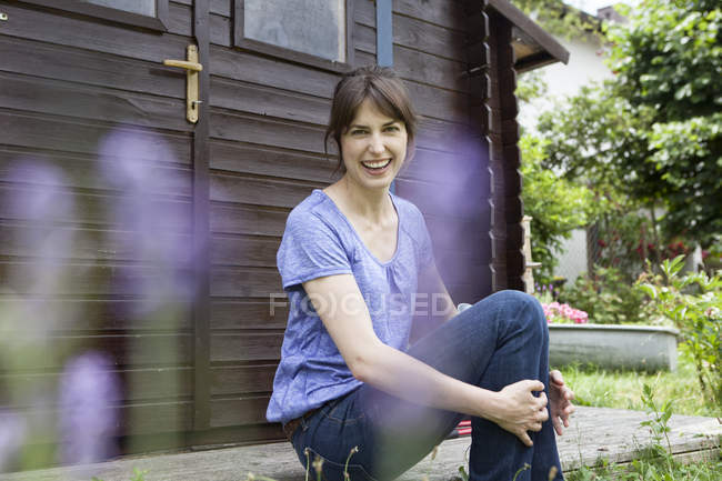 Happy caucasian woman sitting at garden shed — Stock Photo