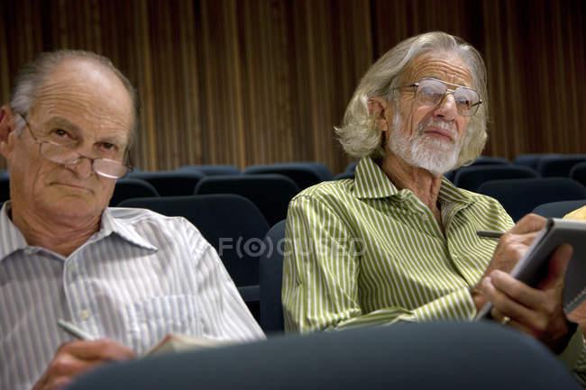 Two senior men sitting in auditorium and taking notes — Stock Photo
