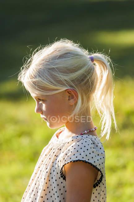 Profilo di Blond little girl standing in nature — Foto stock