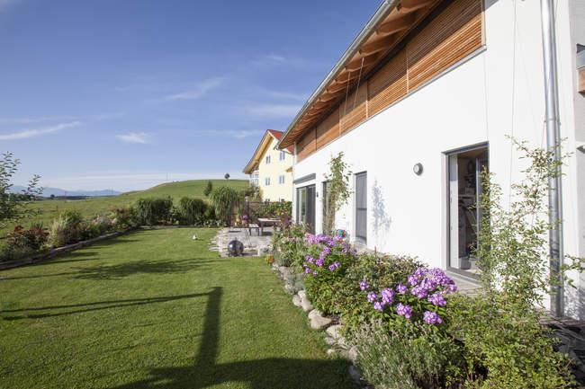 Casa unifamiliar con jardín durante el día - foto de stock