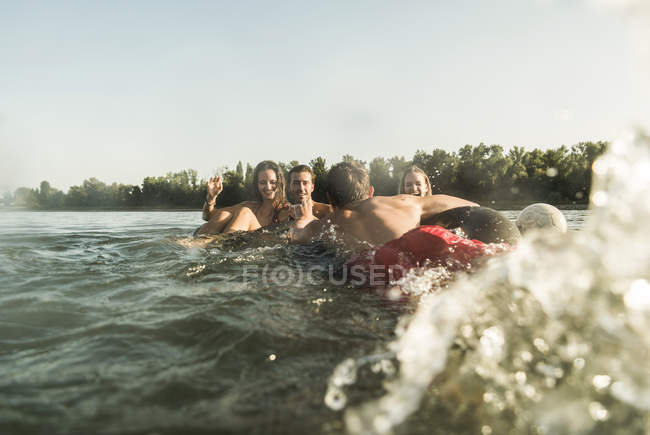 Happy friends swimming and splashing in river — Stock Photo