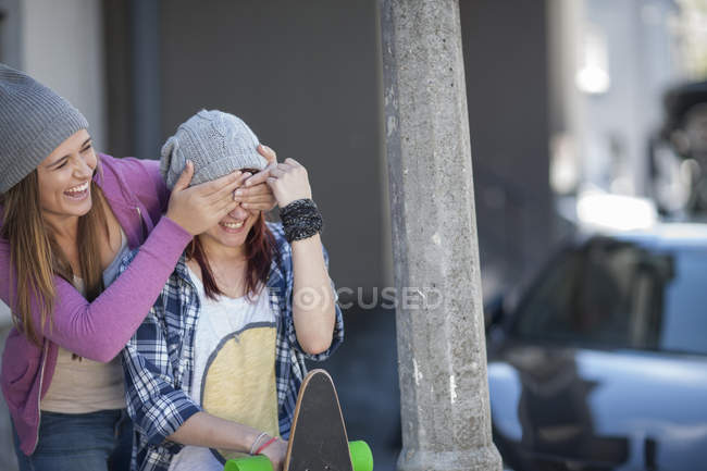 Two playful female friends with skateboard — Stock Photo