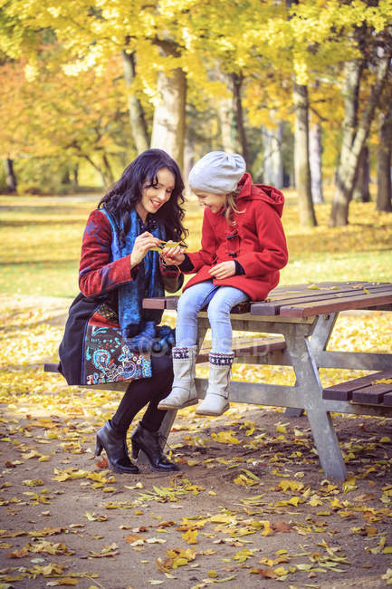 Mother with daughter in autumnal park examining leaf — Stock Photo