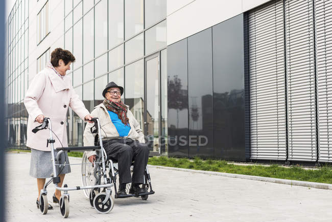 Senior woman with wheeled walker and senior man in wheelchair on pavement — Stock Photo