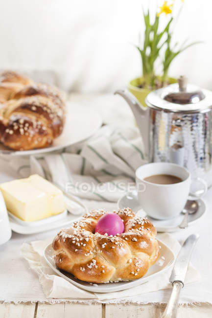 Braided Easter bread with pink egg, coffee and butter — Stock Photo