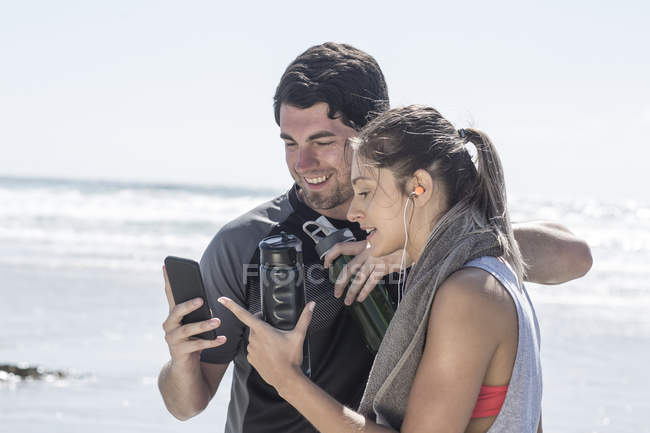 Sportive man and woman on beach looking at cell phone — Stock Photo