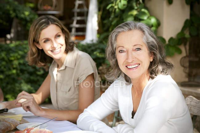 Portrait de femme mûre souriante et jeune femme en arrière-plan — Photo de stock