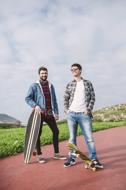 Two happy friends standing with longboard and skateboard in nature — Stock Photo