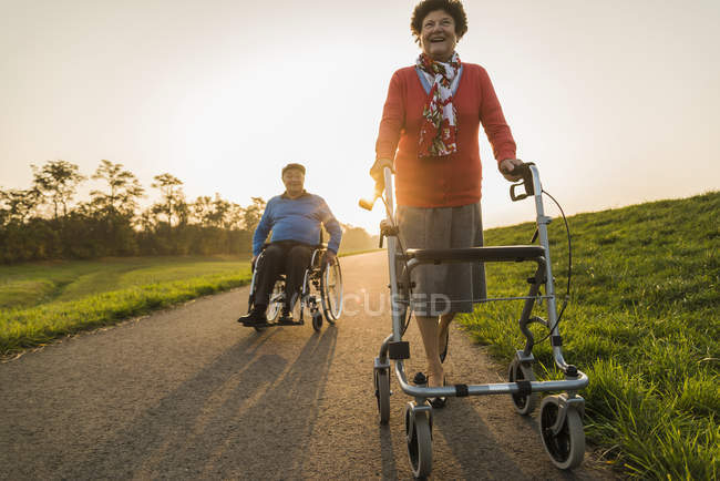 Smiling senior couple with wheelchair and wheeled walker on a path — Stock Photo