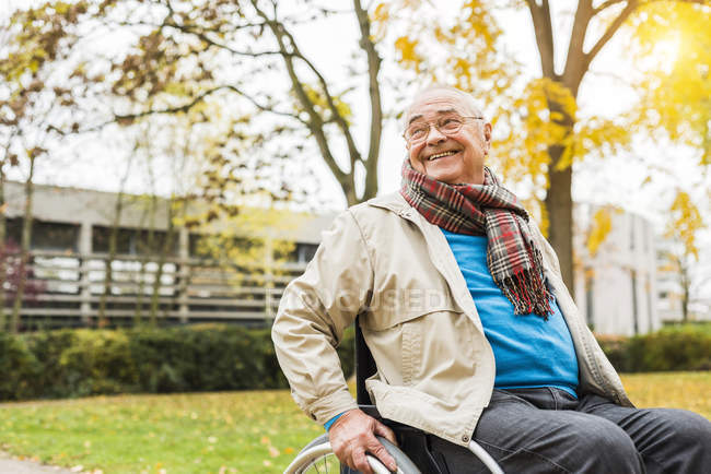 Smiling senior man in wheelchair outdoors — Stock Photo