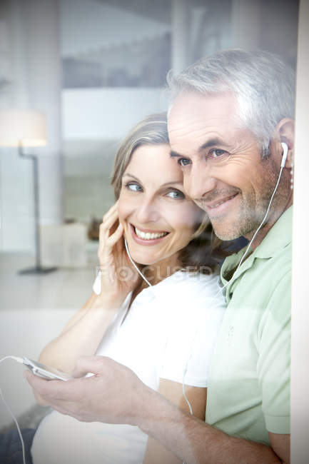 Portrait of smiling couple with earphones and mp3 player looking through window — Stock Photo