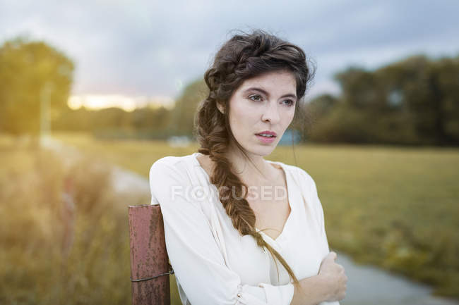 Woman with braid leaning against pole at twilight — Stock Photo