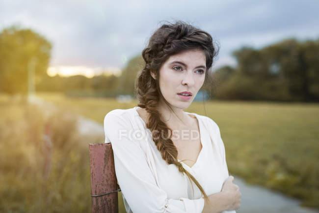 Женщина с косой, прислонившись полюс в сумерках — стоковое фото