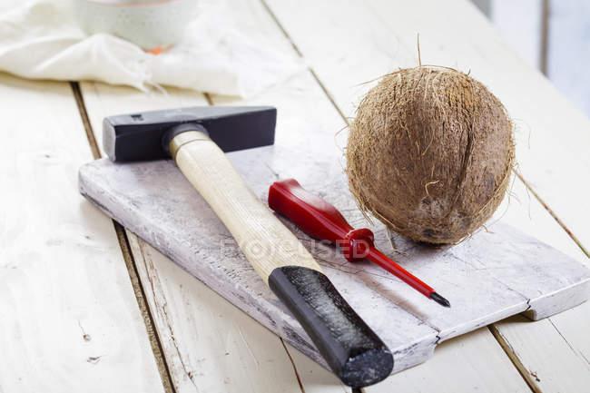 Молоток, викрутка і кокосовим на дерев'яну шахівницю — стокове фото