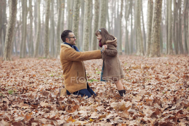 Father playing with his daughter in park sitting in autumnal leaves — Stock Photo