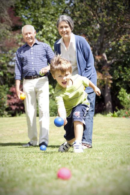 Kleiner Junge mit seinen Großeltern Boccia spielen — Stockfoto