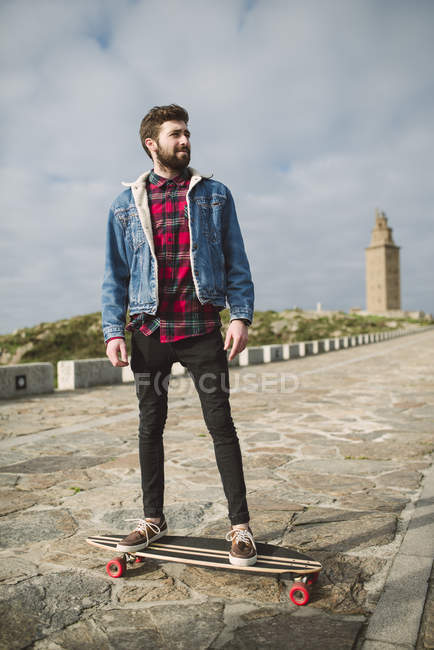 Young hipster man standing on longboard with lighthouse on background — Stock Photo