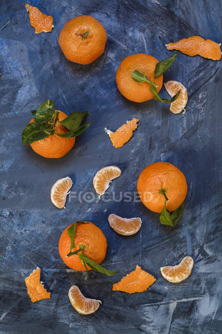 Ansicht von ganzen und geschälten Clementinen auf blauem Hintergrund — Stockfoto