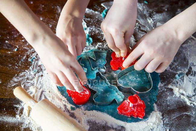 Manos de dos niños cortando galletas de Navidad - foto de stock