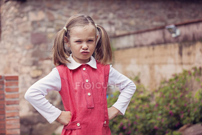 Portrait of little girl with hands on her hips pouting mouth — Stock Photo