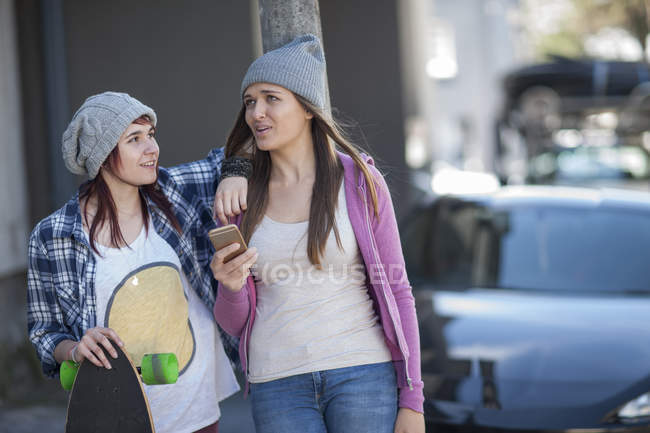 Two stylish female friends with skateboard — Stock Photo