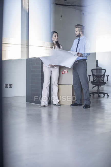 Businesspeople with construction plan in office — Stock Photo