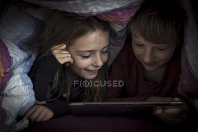 Frère et soeur se trouvant côte à côte à l'aide d'une tablette numérique sous une couverture — Photo de stock