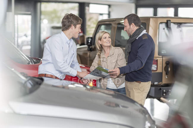 Car dealer talking to couple in showroom — Stock Photo